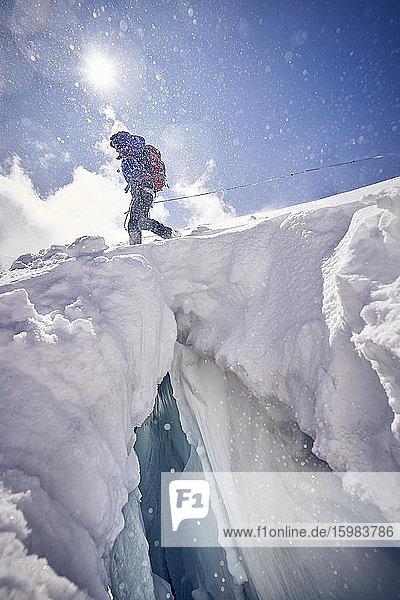 Female mountaineer at crevasse against the sun  Glacier Grossvendediger  Tyrol  Austria