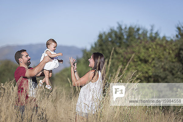 Happy family amidst plants in forest against sky on sunny day