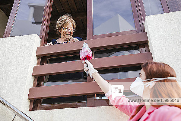 Reporter holding microphone while interviewing senior woman through window