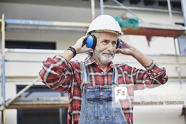 Construction worker with ear muff working at construction site