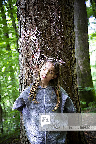 Young girl with eyes closed standing against tree trunk in forest