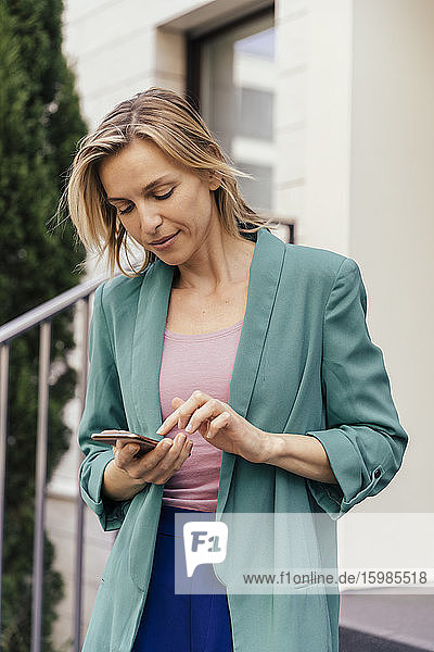 Woman using smart phone at stairs of house