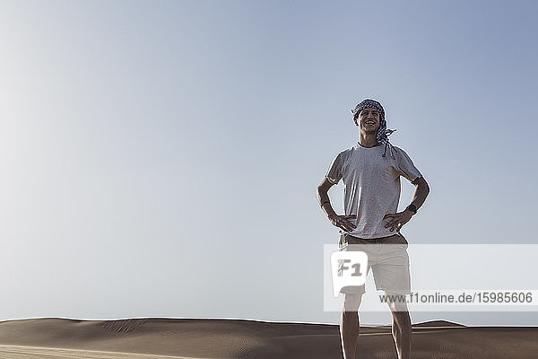 Smiling tourist standing with hands on hip against clear sky at desert in Dubai  United Arab Emirates