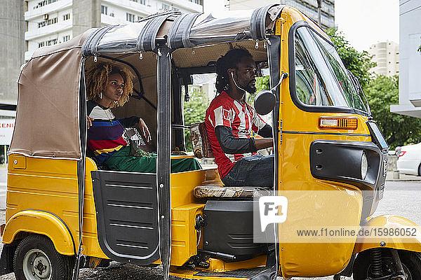 Young woman traveling through tuk-tuk in city