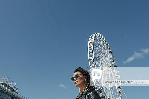 Woman wearing sunglasses near Ferris wheel against blue sky
