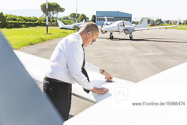 Pilot doing pre flight inspection on his sports plane