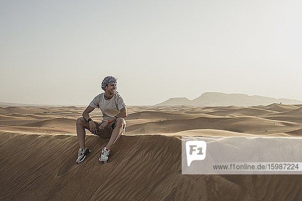 Male tourist looking away while sitting on sand dunes in desert at Dubai  United Arab Emirates