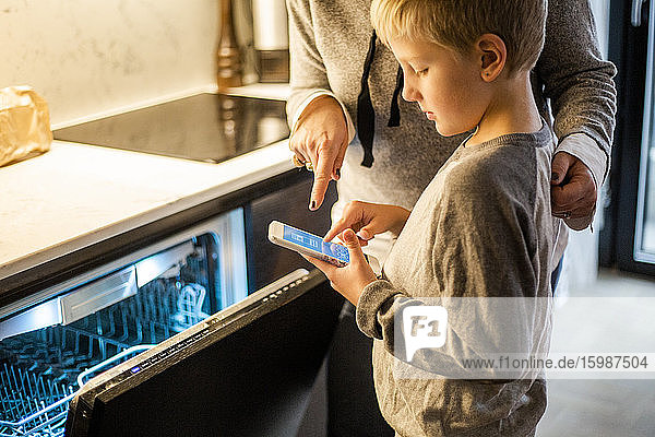 Boy learning from mother while using mobile app over dishwasher in kitchen at smart home