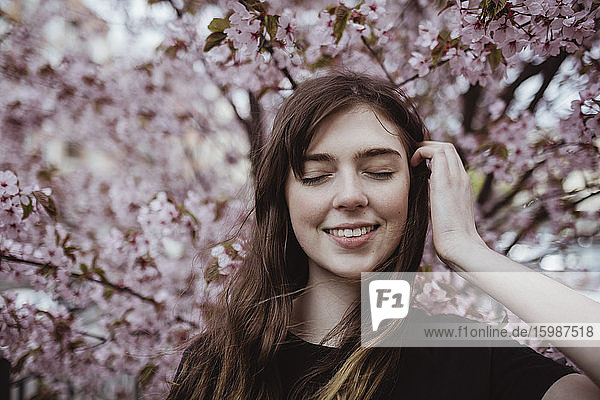 Smiling woman with eyes closed standing against tree