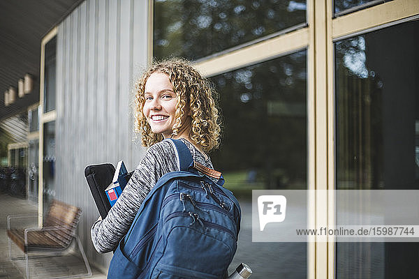 Portrait of smiling young woman with bag at university campus