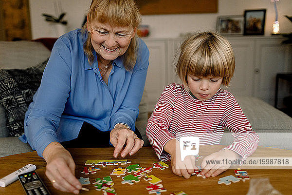 Boy playing jigsaw puzzle with smiling grandmother at home
