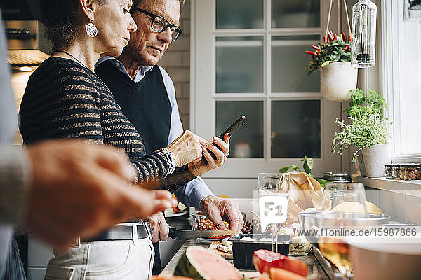 Senior woman showing smart phone to man while preparing dinner in kitchen