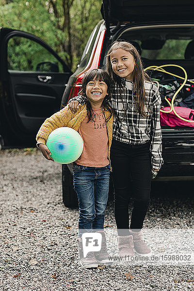 Portrait of smiling sisters standing against electric car