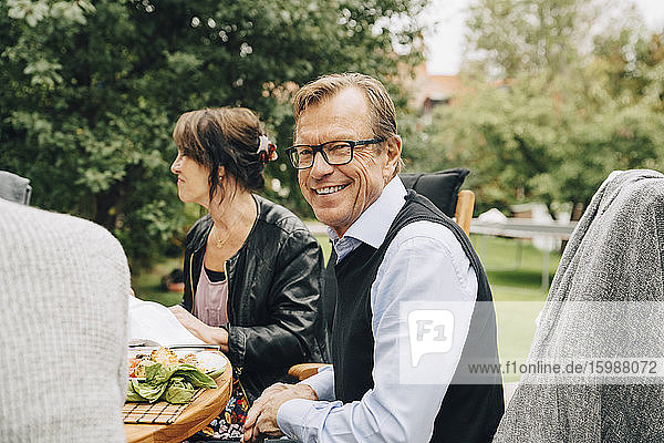 Portrait of smiling senior man sitting with friends at dining table in back yard