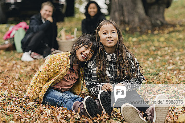 Portrait of smiling sisters sitting on autumn leaves during picnic with parents