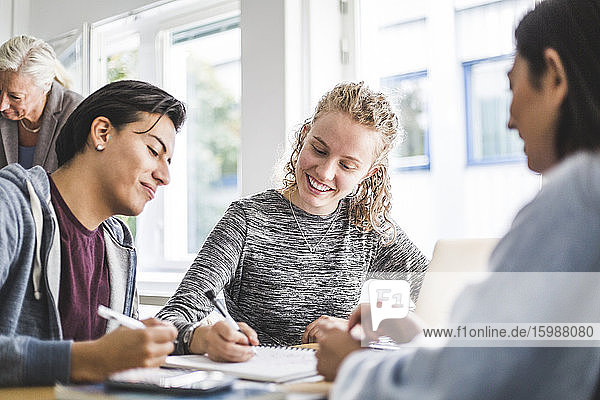 Smiling young woman discussing with male friend over book in classroom