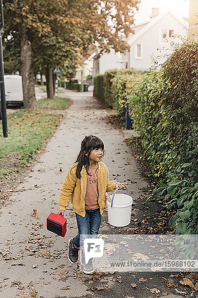 Girl carrying bucket while walking on footpath