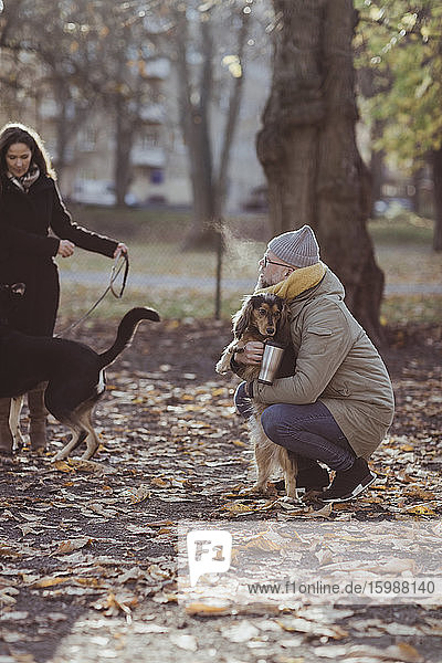 Full length of man crouching while embracing dog by woman with pet at park