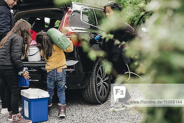 Familie lädt Gepäck in den Kofferraum  während Frau Elektroauto auflädt Familie lädt Gepäck in den Kofferraum, während Frau Elektroauto auflädt