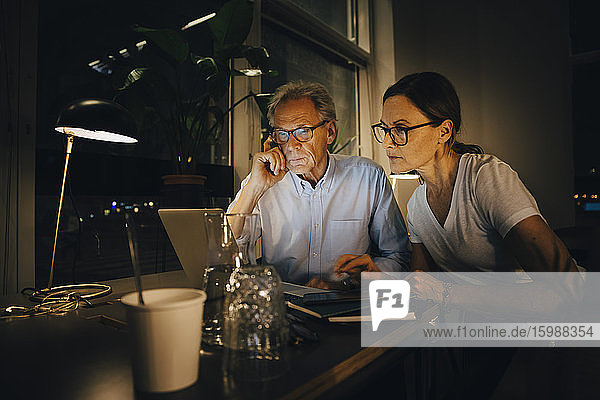 Businesswoman with senior businessman planning strategy in dark office while working late