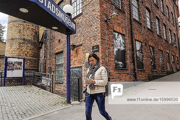 Norrkoping  Sweden Pedestrians walking in the old iconic mill and industrial section of town and the Museum of Work.