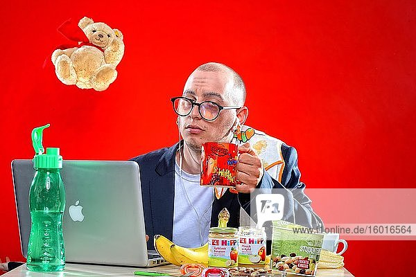 Young man with snacks in front of notebook  Corona Series  Germany  Europe