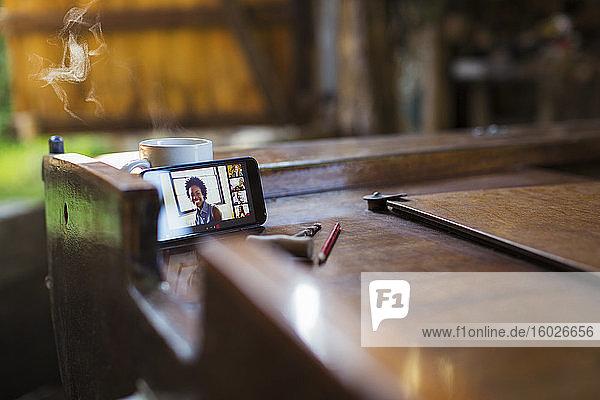 Video-Chat mit Kollegen per Smartphone auf einem Holzboot
