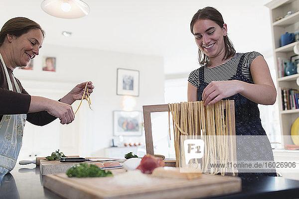 Mutter und Tochter machen in der Küche frische hausgemachte Pasta