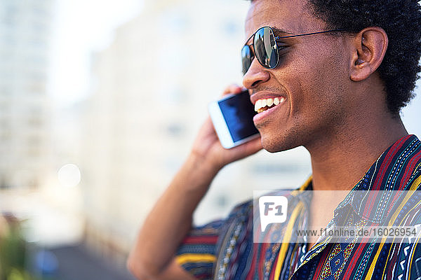 Smiling young man talking on smart phone