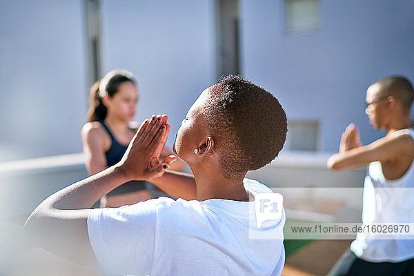 Gelassene junge Frau praktiziert Yoga auf sonnigem Balkon