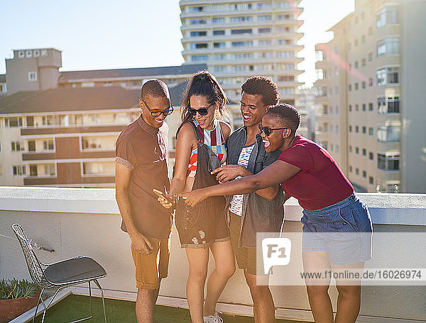 Happy young friends with smart phone on sunny urban balcony