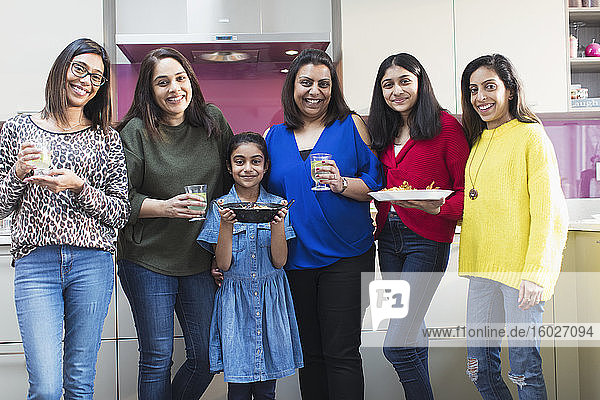 Portrait happy Indian women and girls preparing food in kitchen