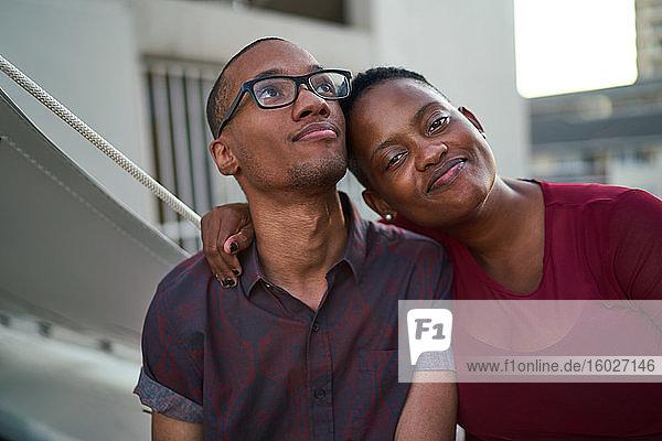 Porträt eines selbstbewussten  liebevollen jungen Paares  das sich auf der Terrasse umarmt