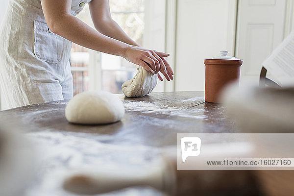 Teenager-Mädchen knetet Teig beim Backen in der Küche