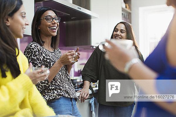 Happy women drinking tea in kitchen