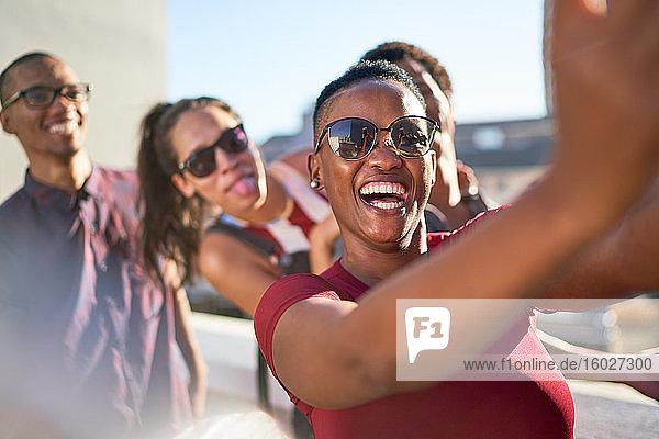Fröhliche  verspielte junge Freunde  die sich auf der sonnigen Terrasse vergnügen