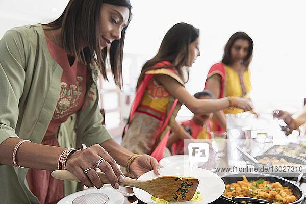 Indische Frauen in Saris beim Servieren von Essen