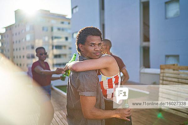 Porträt eines jungen Paares  das sich umarmt und Bier auf dem Dach einer Stadt trinkt