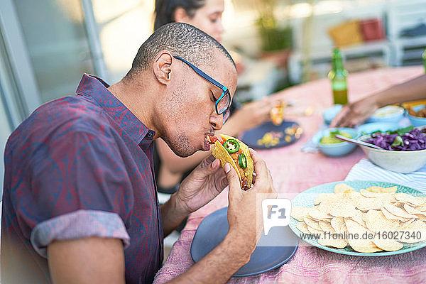 Junger Mann isst Taco am Terrassentisch