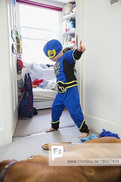 Junge im Superheldenkostüm spielt zu Hause