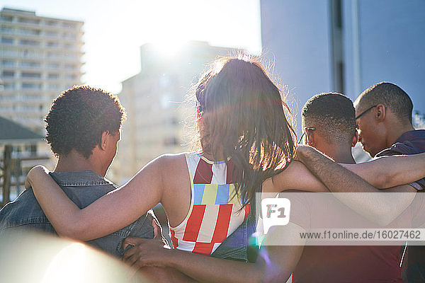 Young friends hugging and hanging out on sunny rooftop balcony