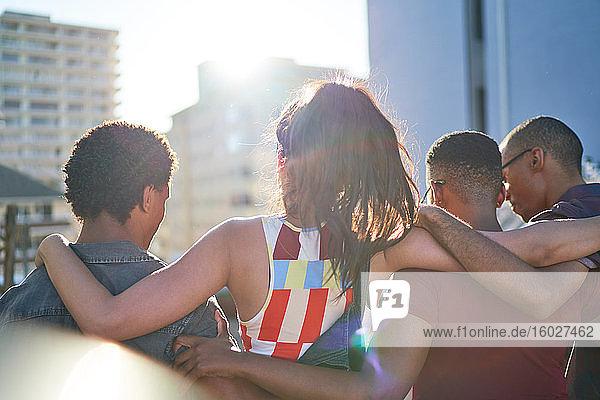 Junge Freunde umarmen sich und hängen auf dem sonnigen Balkon auf dem Dach herum