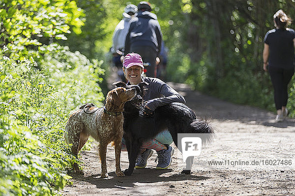 Happy woman hiking on sunny trail with dogs