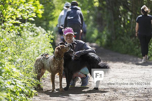 Glückliche Frau wandert mit Hunden auf sonnigem Pfad