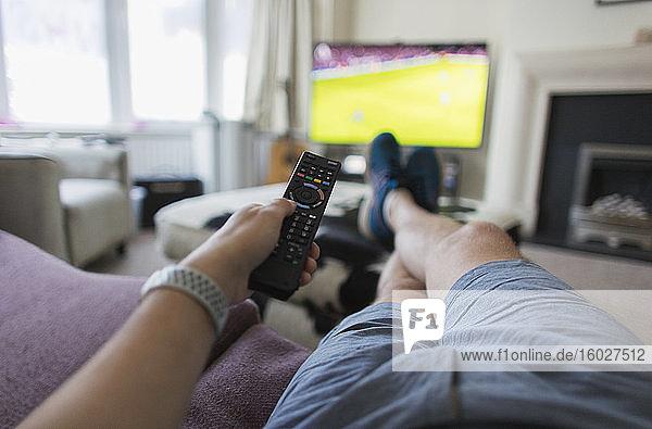 POV-Mann mit Fernbedienung sieht Fußballspiel auf Wohnzimmer-Sofa