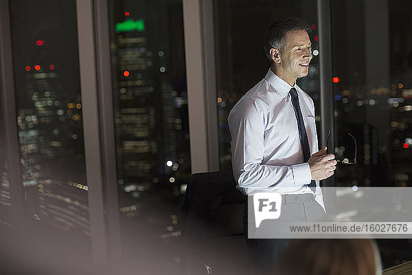 Businessman smiling in office at night