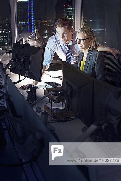 Geschäftsleute  die spät am Computer im Büro arbeiten