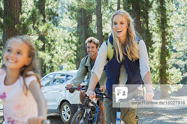 Smiling family riding mountain bikes in woods
