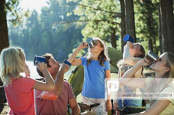 Familie trinkt aus Bechern auf einem Campingplatz im Wald