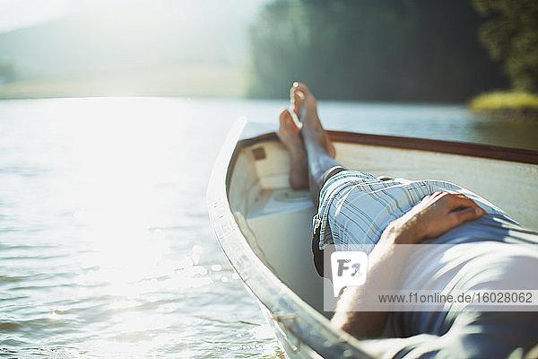 Mann liegt im Ruderboot auf ruhigem See Mann liegt im Ruderboot auf ruhigem See